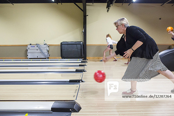 Caucasian woman releasing bowling ball in lane
