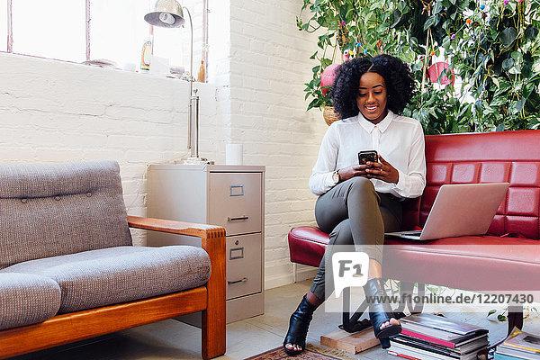 Frau im Büro sitzt auf dem Sofa mit Laptop und schreibt SMS auf Smartphone