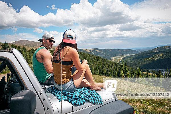 Auf der Motorhaube sitzendes Ausflugspaar in den Rocky Mountains  Breckenridge  Colorado  USA