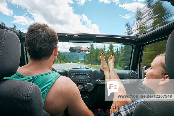 Young woman with feet up driving on road trip with boyfriend  Breckenridge  Colorado  USA