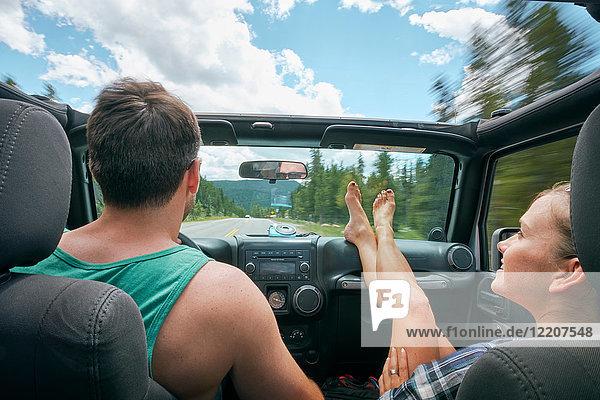 Junge Frau mit hochgezogenen Füßen fährt mit ihrem Freund auf Road Trip  Breckenridge  Colorado  USA