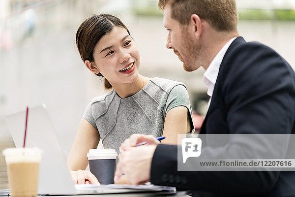 Junger Geschäftsmann und Frau diskutieren im Straßencafé