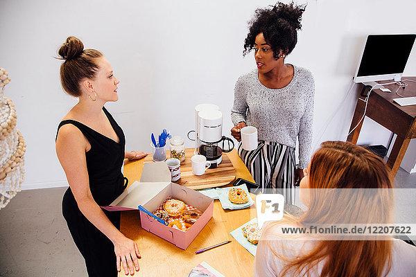 Kollegen im Kaffeebereich teilen sich eine Schachtel Doughnuts