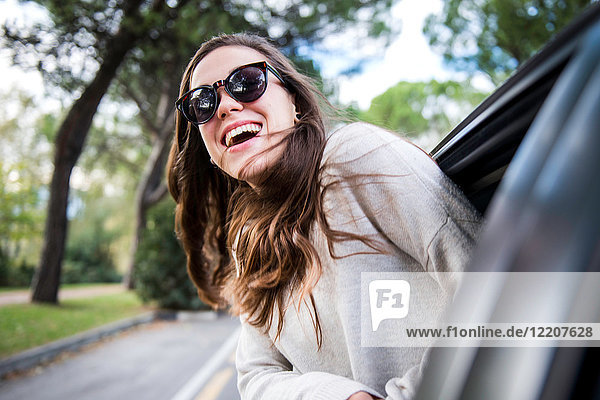 Happy young woman on road trip leaning out of car window