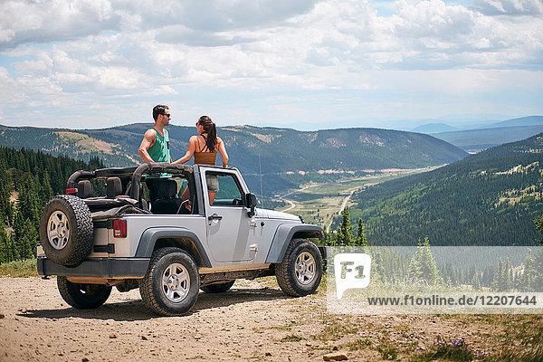 Road trip couple in four wheel convertible in Rocky mountains  Breckenridge  Colorado  USA