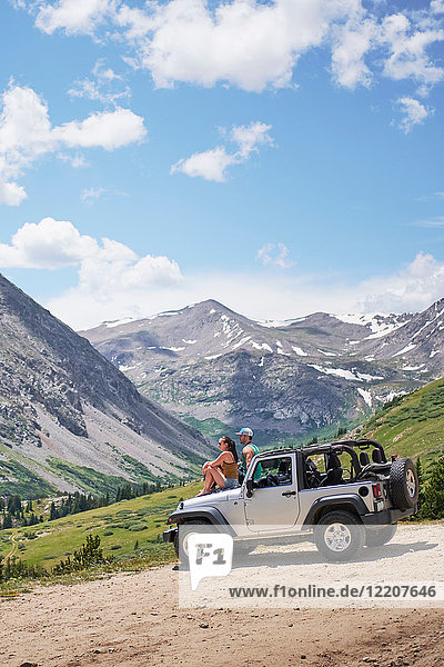 Road trip couple looking out at mountains from off road vehicle hood  Breckenridge  Colorado  USA
