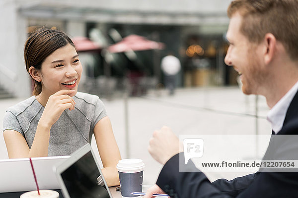 Junge Geschäftsfrau und Mann diskutieren im Straßencafé