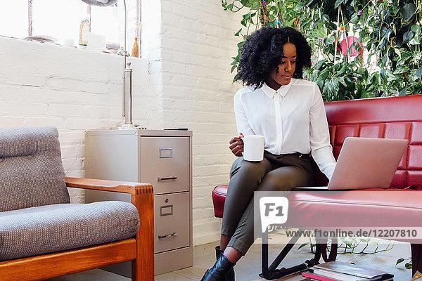Frau im Büro sitzt mit Laptop auf dem Sofa