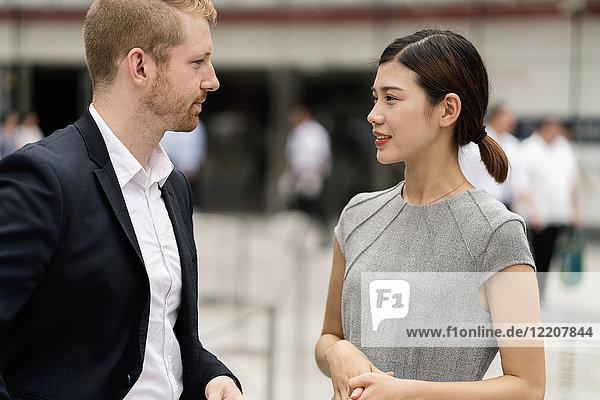 Junger städtischer Geschäftsmann und junge Geschäftsfrau treffen sich im Freien