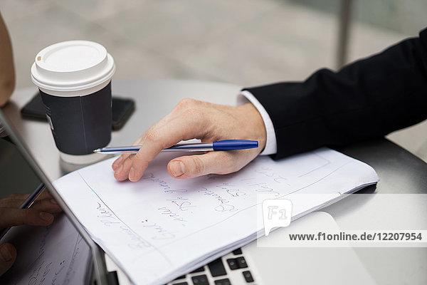 Junger städtischer Geschäftsmann erledigt Papierkram im Bürgersteig-Café  Nahaufnahme