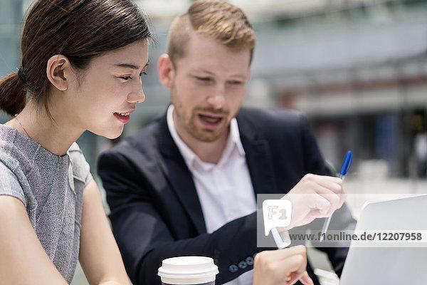 Junge Geschäftsfrau und Mann schauen auf Laptop im Straßencafé