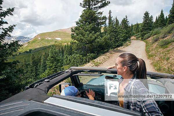 Young woman looking out from four wheel convertible in Rocky mountains  Breckenridge  Colorado  USA