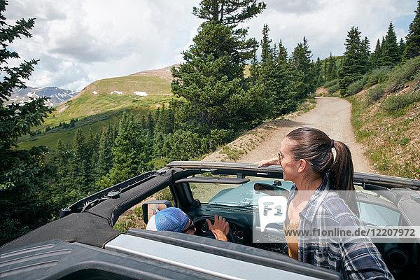 Junge Frau schaut aus einem Vierrad-Cabriolet in den Rocky Mountains  Breckenridge  Colorado  USA