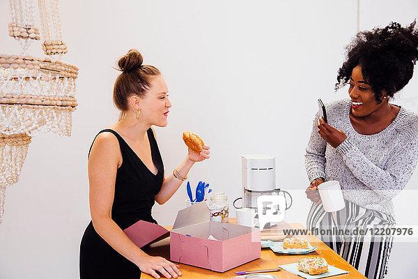 Frau fotografiert Freund beim Donut-Essen