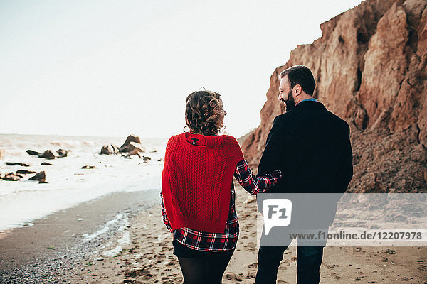 Rückansicht eines romantischen Paares mittlerer Erwachsener  das am Strand spazieren geht  Oblast Odessa  Ukraine