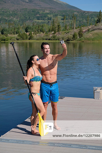 Paddleboarding couple taking selfie on lake pier  Frisco  Colorado  USA