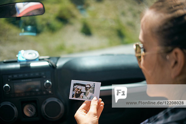 Over shoulder view of young woman on road trip holding instant photograph with boyfriend  Breckenridge  Colorado  USA