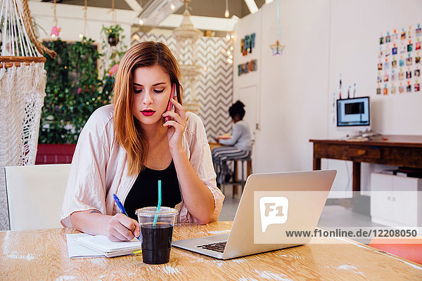 Woman sitting at desk in creative studio making telephone call on smartphone