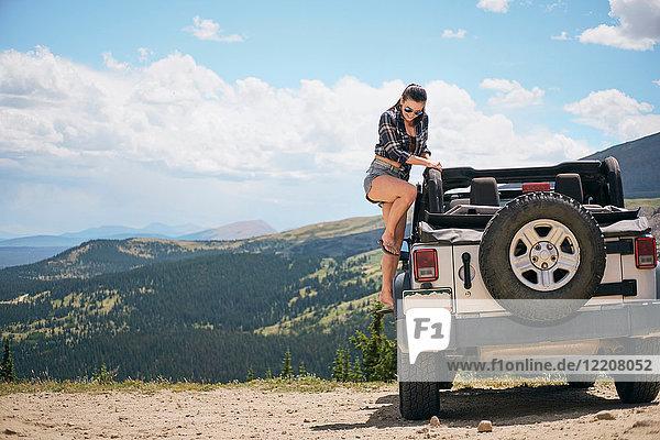 Junge Frau auf Autoreise  die in ein geparktes Geländefahrzeug steigt  Breckenridge  Colorado  USA