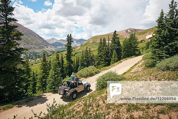 Road trip couple looking out at Rocky Mountains from four wheel convertible  Breckenridge  Colorado  USA