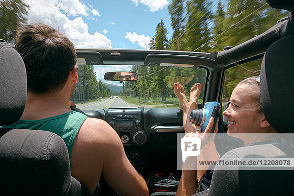 Young woman with instant camera driving on road trip with boyfriend  Breckenridge  Colorado  USA