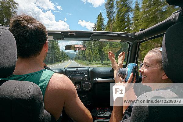 Junge Frau mit Sofortbildkamera fährt auf Road Trip mit ihrem Freund  Breckenridge  Colorado  USA
