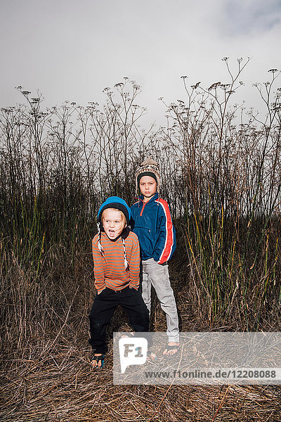 Portrait of two brothers  outdoors  in rural setting  wearing knitted hats