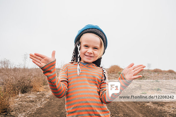 Portrait of boy on in rural setting  gesturing with hands