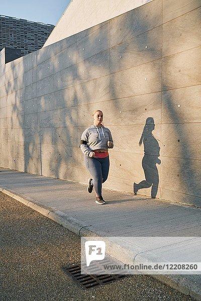Kurvenreiche junge Läuferin läuft auf dem Bürgersteig