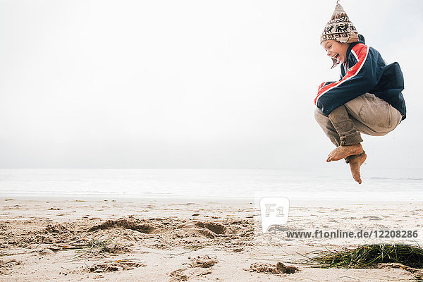 Young boy on beach jumping  mid air