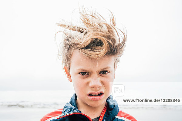 Portrait of boy on beach  messy hair  making face  close-up