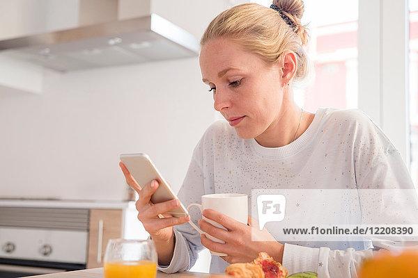 Junge Frau schaut auf Smartphone am Frühstückstisch