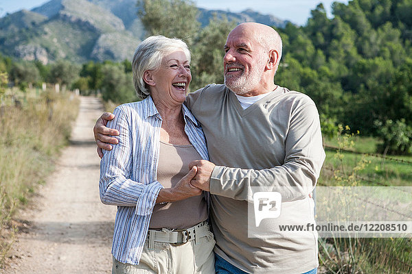 Senior couple walking together in rural setting,  holding hands,  smiling