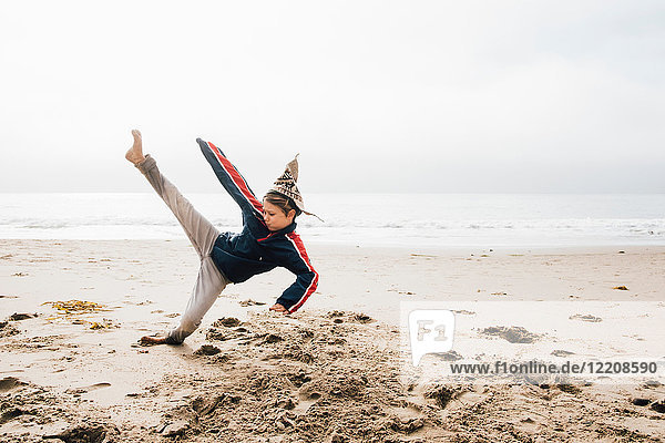 Young boy on beach  practising martial arts  leg raised in kick