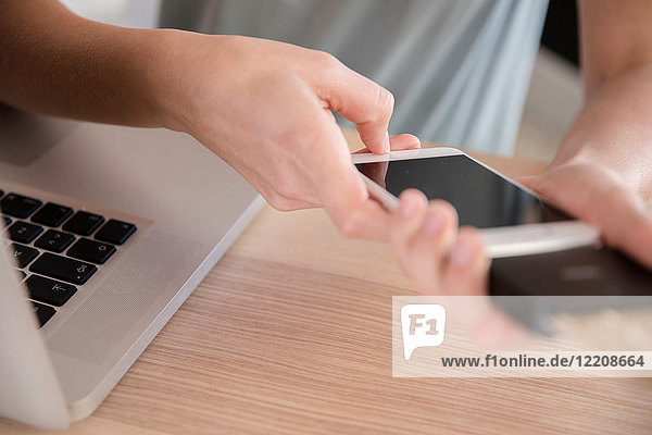 Junge Frau mit Smartphone am Schreibtisch  Nahaufnahme der Hände