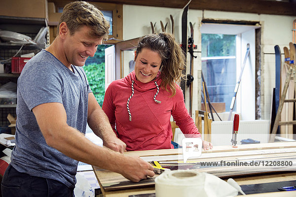 Man and woman in workshop  making ski equipment