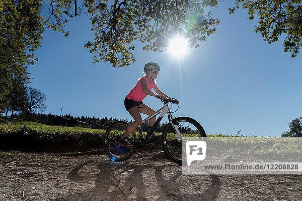 Mountainbike-Mädchen fährt auf sonnenbeschienenem Feldweg