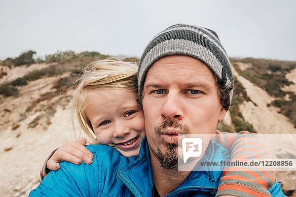 Portrait of father and son  outdoors  smiling  close-up