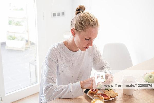 Junge Frau schält Kiwifrüchte am Frühstückstisch