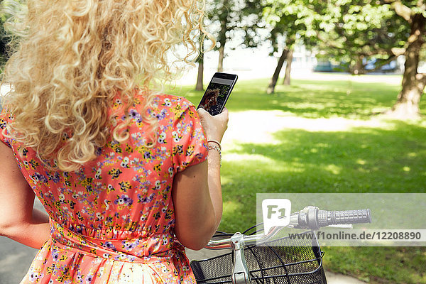Woman with bicycle using smartphone