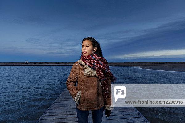 Junge Frau beim Spaziergang am Pier in der Dämmerung  Tarragona  Katalonien  Spanien