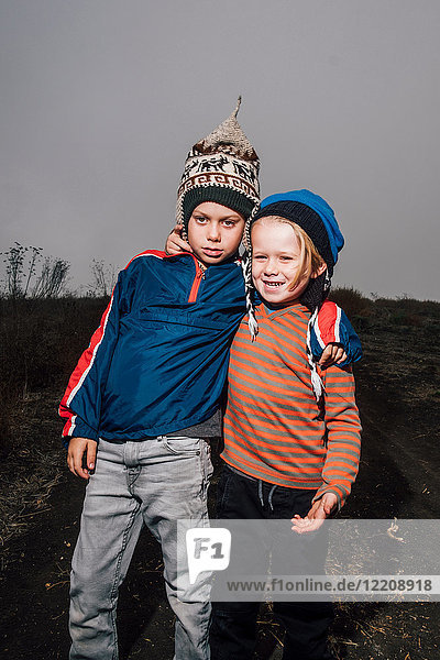 Portrait of two brothers  outdoors  wearing knitted hats  arms around each other