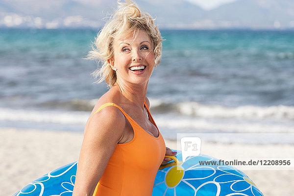 Ältere Frau trägt Hüpfburg am Strand  Palma de Mallorca  Spanien