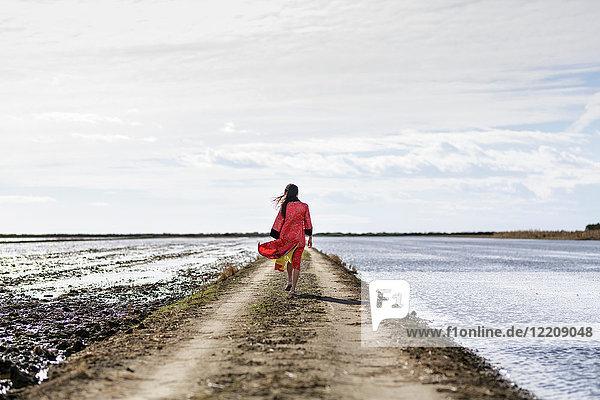 Rückansicht einer jungen Asiatin auf einem Feldweg auf dem Meer in traditioneller Kleidung  Tarragona  Katalonien  Spanien