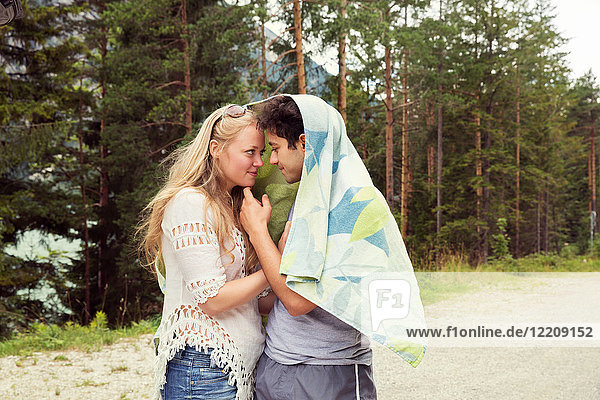 Couple wrapped in towel  face to face hugging