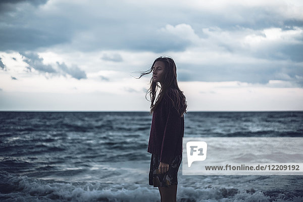 Portrait of young woman standing on beach with eyes closed at dusk  Odessa Oblast  Ukraine