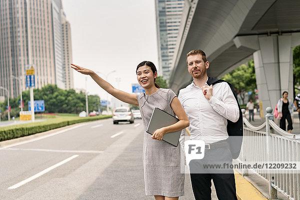 Junge Geschäftsfrau und Mann  die in der Stadt ein Taxi anhalten  Shanghai  China