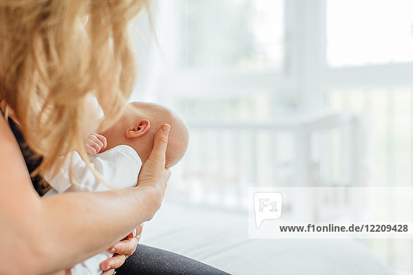 Junge Frau beim Stillen ihrer Tochter  geschoren