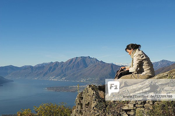 Woman Relax on a Mountain Top with Alpine Lake Maggiore in Background in Ticino  Switzerland.