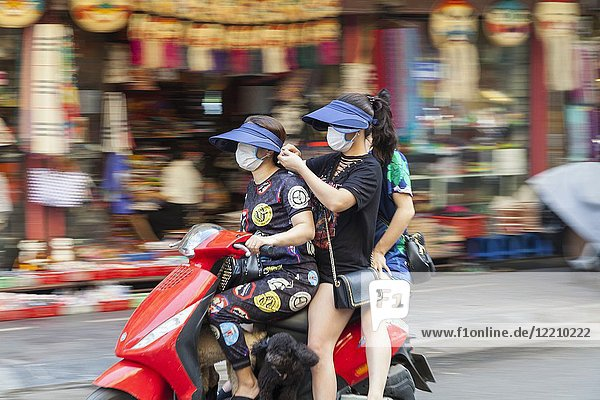 Woman driving on scooter or motorcycle in Hanoi  Vietnam.